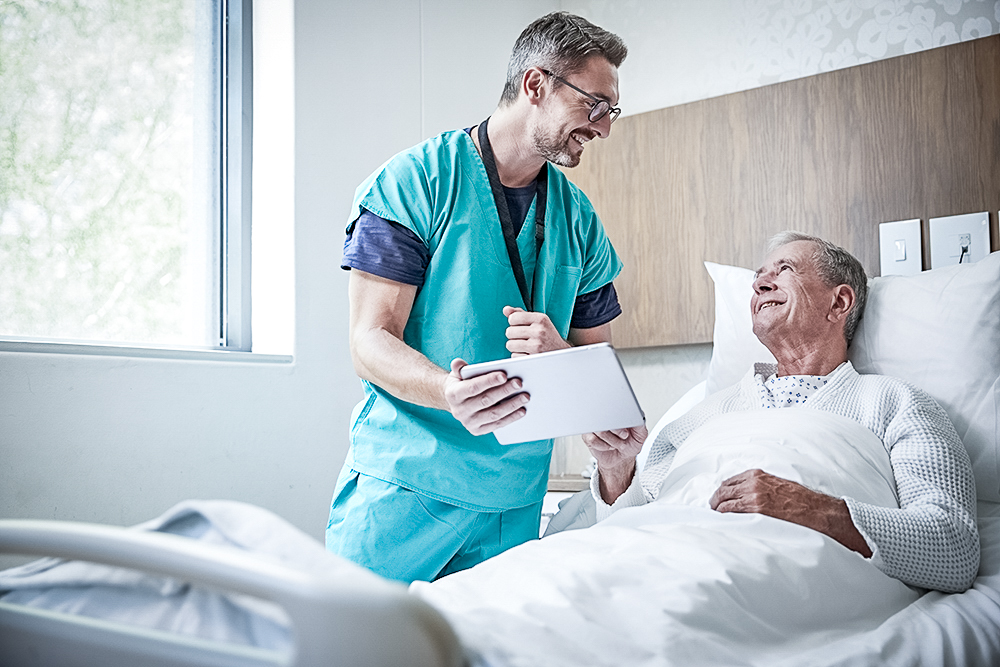 Nurse helping hospital patient in bed